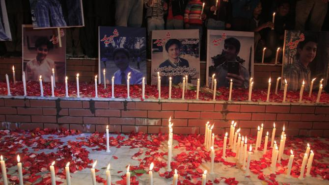 People place pictures of victims of the Pakistan Taliban attack on the Army Public School, during a candle light vigil in Islamabad