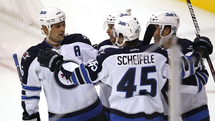 Winnipeg Jets' Mark Stuart, left, Kevin Clark, center, and Ben Maxwell, right, celebrate a goal by forward Mark Scheifele (45) against the Columbus Blue Jackets during the first period of a preseason NHL hockey game in Winnipeg, Manitoba, on Tuesday, Sept. 20, 2011. (AP Photo/The Canadian Press, John Woods)