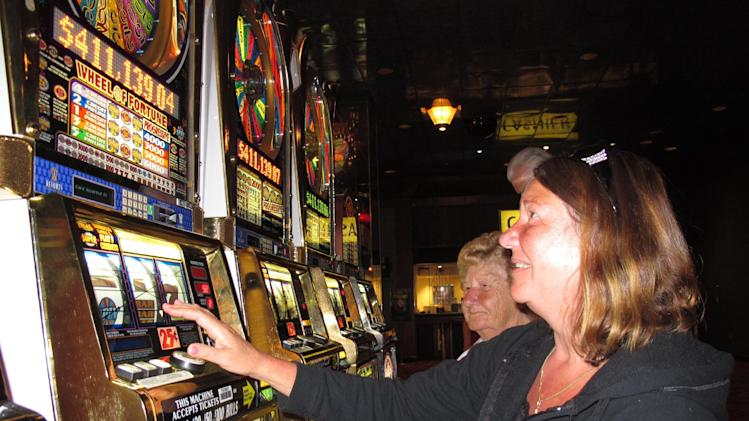 In this Aug. 23, 2012 photo, Carol Gleason of Saddle Brook N.J., foreground, plays a slot machine at Resorts Casino Hotel in Atlantic City N.J. on Aug. 23, 2012. Resorts took in $13 million from gamblers in August. Atlantic City's 12 casinos collectively won nearly $314 million, an increase of 12.6 percent from a year ago, when a hurricane closed the casinos for three days. (AP Photo/Wayne Parry)