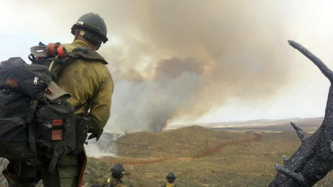 """FILE - In this file photo shot by firefighter Andrew Ashcraft, members of the Granite Mountain Hotshots watch a growing wildfire that later swept over and killed the crew of 19 firefighters near Yarnell, Ariz., Sunday, June 30, 2013. Ashcraft texted the photo to his wife, Juliann, but died later that day battling the out-of-control blaze. The 29-year-old father of four added the message, """"This is my lunch spot...too bad lunch was an MRE."""" (AP Photo/Courtesy of Juliann Ashcraft, File)"""