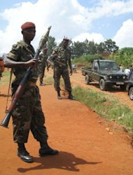 Burundian soldiers stand at a check point in Kabezi, 20 km south of Bujumbura. Monday will see the police and army march across Burundi's capital in brand new Chinese-made uniforms, estimated to have cost the country $1.5 mn