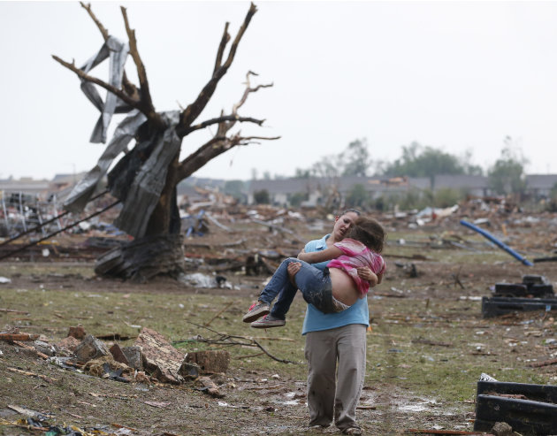 A woman carries her child through a field near the collapsed Plaza Towers Elementary School in Moore, Okla., Monday, May 20, 2013. A tornado as much as a mile (1.6 kilometers) wide with winds up to 20