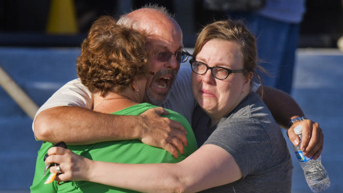 "FILE - In this Friday, July 20, 2012 file photo, Tom Sullivan, center, embraces family members outside Gateway High School where he has been searching franticly for his son Alex Sullivan who celebrated his 27th birthday by going to see ""The Dark Knight Rises,"" movie where a gunman opened fire, in Aurora, Colo. (AP Photo/Barry Gutierrez)"