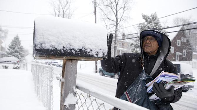 U.S. Postal Service mail carrier Willian Heredia delivers mail during snowstorm in Catonsville, Md., Thursday, March 5, 2015. The U.S. federal government said its offices in the Washington area will be closed Thursday because of a new round of winter weather expected in the region. The Office of Personnel Management said non-emergency personnel in and around Washington were granted excused absences for the day. Emergency employees and telework-ready employees were expected to work (AP Photo/Carolyn Kaster)