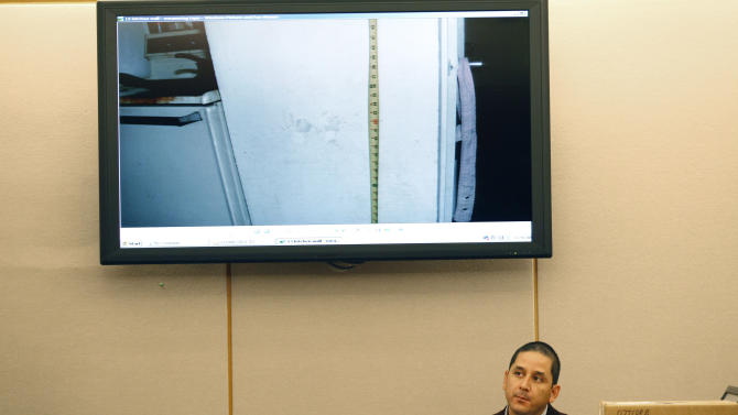 Dallas police officer Abel Lopez listens to a question in front of a display showing a crime scene photo of little hand prints on a wall while testifying about his investigation at the apartment of Elizabeth Escalona, 23, not shown, in Dallas, Monday, Oct. 8, 2012. Escalona pleaded guilty July 12, 2012, to injury to a child and is facing up to life in prison. A doctor has testified that the Texas mother glued her 2-year-old daughter's hands to a wall and beat the toddler so badly that she suffered significant brain trauma and bleeding inside her skull.(AP Photo/LM Otero)