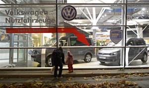 A woman and a child look at cars of German carmaker Volkswagen in a shop of a VW dealership in Hamburg
