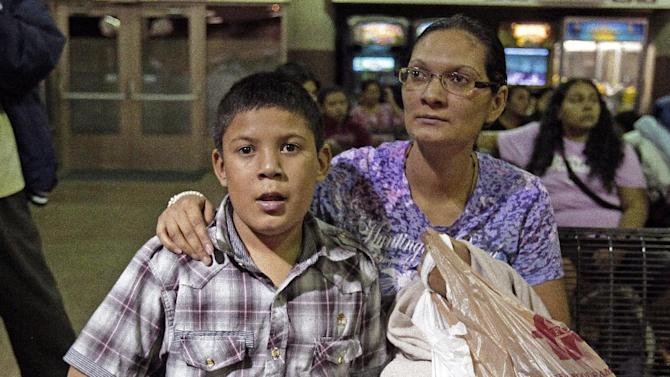 FILE - In this May 29, 2014 file photo, Maria Eva Casco, left, and her son Christian Casco of El Salvador, sit at at the Greyhound bus terminal, Thursday, May 29, 2014 in Phoenix. Central American families arrested in Texas will continue to be flown to Arizona, and hundreds of unaccompanied minors a day are being shipped to a federal detention center in the southern part of the state, Gov. Jan Brewer's spokesman says. (AP Photo/Rick Scuteri)