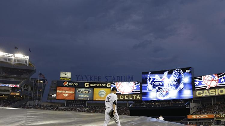 Under a threatening sky, New York Yankees starting pitcher Hiroki Kuroda (18) heads to the bullpen for warmup before a baseball game against the Boston Red Sox at Yankee Stadium in New York, Sunday, June 2, 2013. (AP Photo/Kathy Willens)