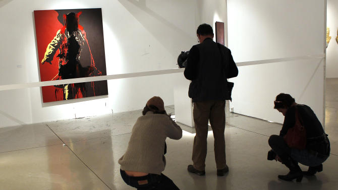 The controversial portrait of South African President Jacob Zuma painted by Brett Murray stands defaced  at the Goodman Gallery in Johannesburg, South Africa, Tuesday May 22, 2012. Footage shown on a national news station showed a man in a suit painting a red X over the president's genital area and then his face. Next a man in a hoodie rubbed black paint over the president's face and down the painting with his hands. (AP Photo/Jerome Delay)