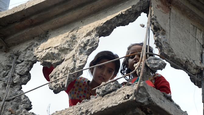 Pakistani Kashmiri girls look through a damaged wall hit by a mortar during cross border shelling, in Nakyal Sector, on the heavily militarised Line of Control (LoC) in Pakistan-administered Kashmir on August 18, 2015
