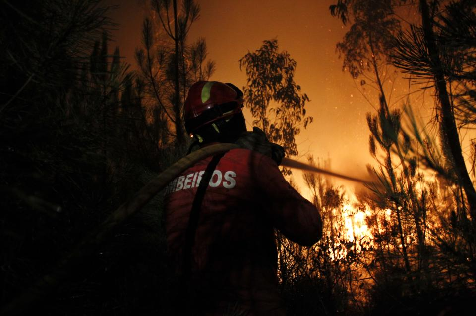 A firefighter works to douse the fire in Ribeira do Farrio, near Ourem, Portugal, Monday, Sept. 3, 2012. A Portuguese official says authorities have asked other European countries to send help as the country's firefighters struggle to contain forest blazes being fueled by high temperatures and strong winds. (AP Photo/Francisco Seco)