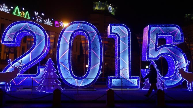 A man walks past a festive street decoration, which marks the upcoming New Year in Almaty