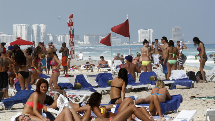 In this March 10, 2012 photo, people hang out on the beach during spring break in Cancun, Mexico. While American tourism to Mexico slipped a few percentage points last year, the country remains by far the biggest tourist destination for Americans, according to annual survey of bookings by the largest travel agencies. (AP Photo/Israel Leal)