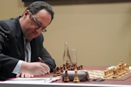 Israel's Boris Gelfand takes notes during a world chess championship match in Moscow this week. Gelfand, dressed in a suit without a tie, spends little time in his specially configured seat, taking long strolls across the stage with his hands firmly clasped behind his back