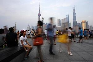 People walk along the Bund in front of the financial district of Pudong, in downtown Shanghai