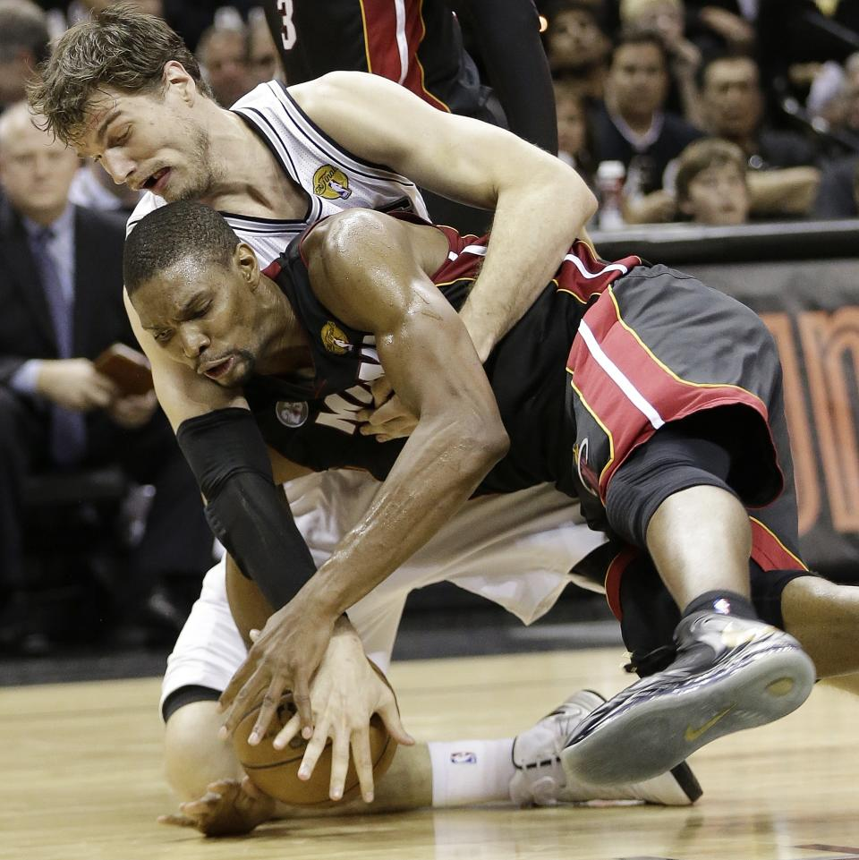 San Antonio Spurs' Tiago Splitter, of Brazil, and Miami Heat's Chris Bosh go after the ball during the first half at Game 5 of the NBA Finals basketball series, Sunday, June 16, 2013, in San Antonio. (AP Photo/Eric Gay)