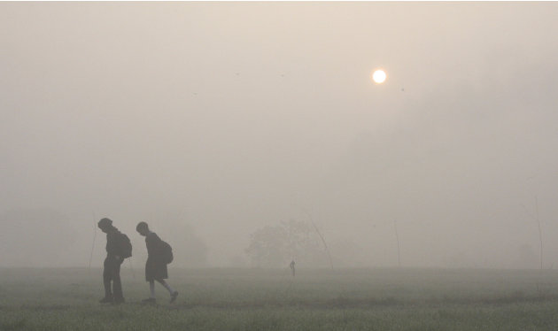 Students walk towards their school amid heavy fog on the outskirts of Chandigarh