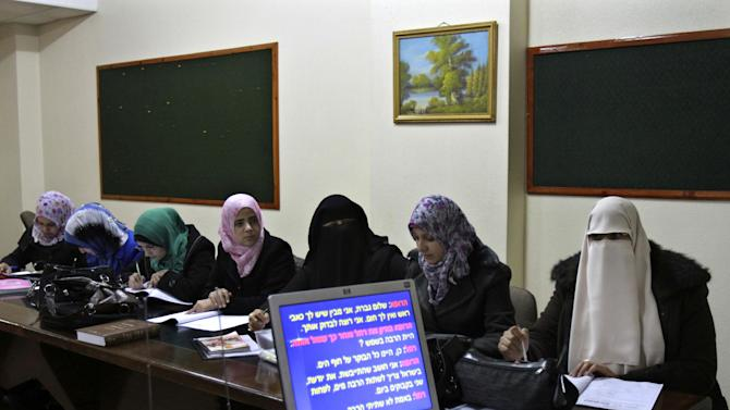 "In this Monday, Jan. 7, 2013 photo, Palestinian students study Hebrew at the Islamic University in Gaza City. Gaza's Islamic University, a stronghold of the ruling Hamas militant group, has started its first Hebrew-language class. Hamas, which has killed hundreds of Israelis in years of battles against the Jewish state, says its aim is simple: Palestinians should learn their enemy's language: ""As Jews are occupying our lands, we have to understand their language,"" says an Education Ministry official. (AP Photo/Adel Hana)"