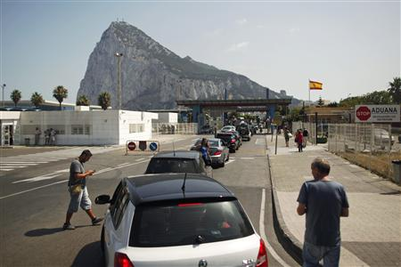 Drivers wait in line to enter the British territory of Gibraltar at its border with Spain in front of the Rock of Gibraltarin La Linea de la Concepcion
