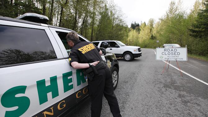 Sheriff's deputies talk at a blocked road heading several miles from where a gun-toting survivalist is suspected of killing his wife and daughter several days earlier Friday, April 27, 2012, in North Bend, Wash. Peter Alex Keller may be holed up in a self-made fort not far from where Seattle's outer suburbs give way to the vast recreational playground of Cascade Mountains. Police expect more people to hit the nearby trails this weekend, and deputies are warning them to steer clear of Keller if they think they see him.  (AP Photo/Elaine Thompson)