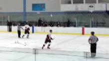 A hockey coach throws a water bottle in the direction of an official at a minor league hockey game.