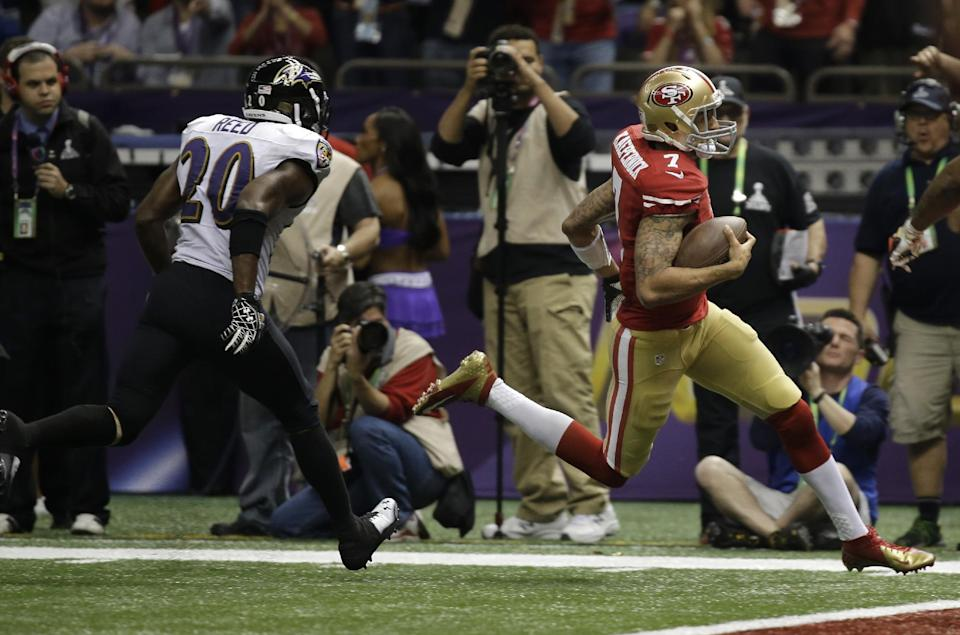San Francisco 49ers quarterback Colin Kaepernick (7) runs toward the end zone for a 15-yard touchdown as he is followed by Baltimore Ravens safety Ed Reed (20) during the second half of the NFL Super Bowl XLVII football game, Sunday, Feb. 3, 2013, in New Orleans. (AP Photo/Matt Slocum)