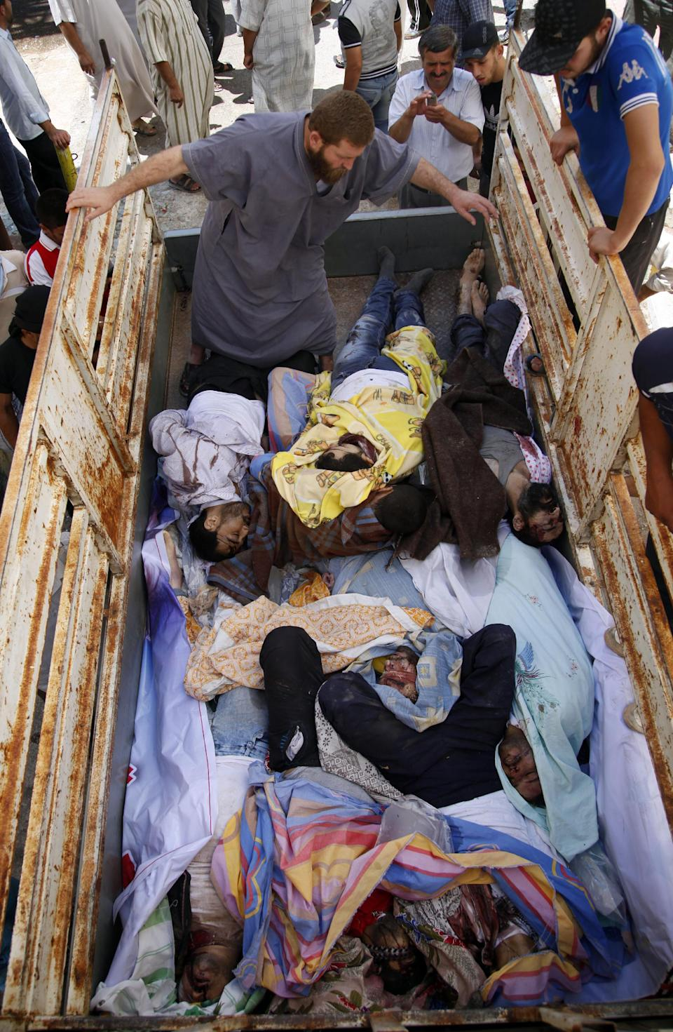 Syrians look at nine bodies of Syrians who were found dead near the town of Anadan outskirts of Aleppo, Syria, Monday, Aug. 6, 2012. (AP Photo)