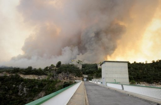 Wildfire is seen from the Boadellas reservoir on July 23, in Darnius, near La Junquera, close to the Spanish-French border. Hundreds of firefighters, backed by water-bombing planes, are battling the wind-fuelled fire in northeast Spain that so far has killed four people, including a teenage girl.