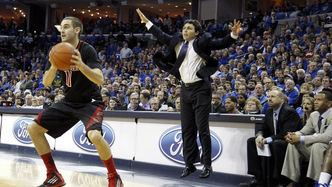 Memphis head coach Josh Pastner calls out a play as his team takes on Louisville forward Luke Hancock (11) and the Louisville Cardinals in the first half of an NCAA college basketball game on Saturday, Dec. 15, 2012, in Memphis, Tenn. (AP Photo/Lance Murphey)