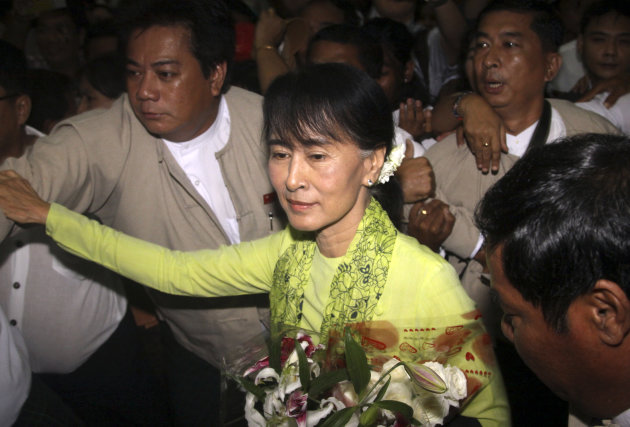 In this Sunday, Sept. 16, 2012 photo, Myanmar opposition Leader Aung San Suu Kyi, center, arrives at Yangon International airport, Myanmar, to depart for the U.S. in Yangon. Suu Kyi left Sunday on her