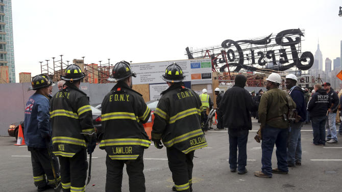 "Firefighters, police officers and construction workers work the scene of a crane collapse at a construction site in the Queens borough of New York, Wednesday, Jan. 9, 2013, behind a big neon ""Pepsi Cola"" sign, a local landmark. The Fire Department of New York says the 200-foot crane collapsed onto a building under construction, injuring seven people, three of them seriously. (AP Photo/Mary Altaffer)"