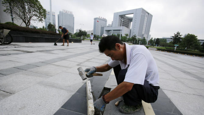 A construction worker arranges tiles of a sidewalk in front of the Hefei City Intermediate People's Court Wednesday, Aug. 8, 2012 in Hefei, Anhui Province, China. The murder trial of Gu Kailai, wife of ousted Chinese politician Bo Xilai, will start Thursday. (AP Photo/Eugene Hoshiko)