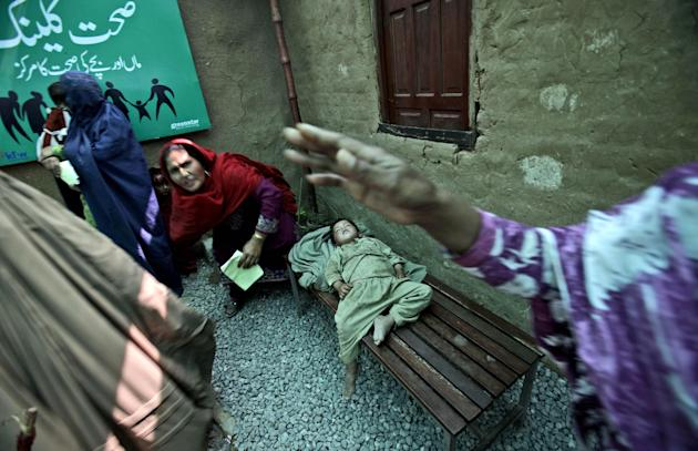 In this Wednesday, April 18, 2012, photo, an Afghan refugee boy, center, sleeps on a bench, while his mother waits her turn to receive free medicine from a clinic, in a slum on the outskirts of Islama