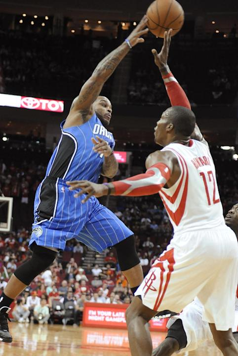 Orlando Magic's Jameer Nelson (14) tries to shoot over Houston Rockets' Dwight Howard (12) in the first half of an NBA basketball game Wednesday, Oct. 16, 2013, in Houston