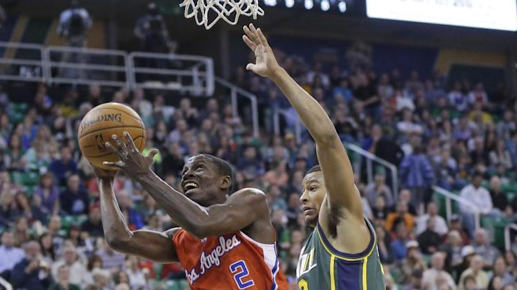 Los Angeles Clippers' Darren Collison (2) goes to the basket as Utah Jazz's Trey Burke, right, defends in the second quarter during an NBA basketball game Friday, March 14, 2014, in Salt Lake City. (AP Photo/Rick Bowmer)