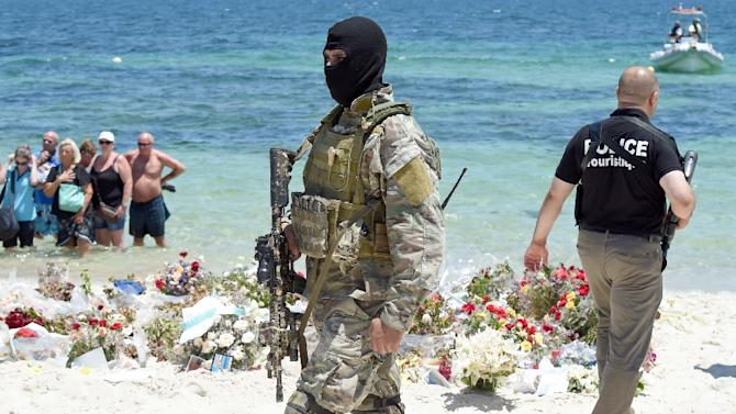 A Tunisian special force officer and a policeman patrol the beach as tourists take part in a ceremony on July 3, 2015, in memory of those killed the previous week by a jihadist gunman in the popular resort of Port el Kantaoui