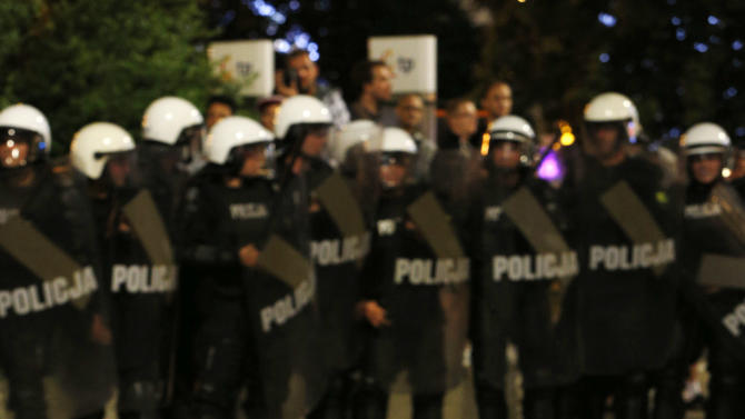 A Polish fan sits in front of special police during clashes between the police and fans during the Euro 2012 soccer championship group a match between Poland and Russia in downtown Warsaw, Poland , Tuesday, June 12, 2012. (AP Photo/Czarek Sokolowski)
