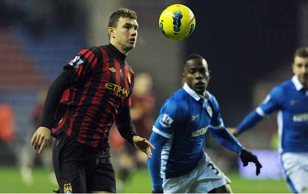 Manchester City's Edin Dzeko (L) Competes With Wigan Athletics's Antolin Alcaraz  RESTRICTED TO EDITORIAL USE. No Use AFP/Getty Images
