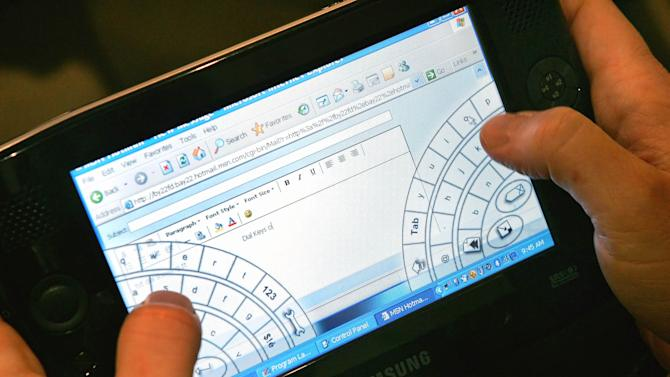 "FILE- In this March 9, 2006, file photo, Microsoft Corporate Vice President William Mitchell  presents a new ultra compact computer by Samsung at the CeBIT computer fair in Hanover, northern Germany.   For decades, the tablet computer was like a mirage in the technology industry: a great idea, seemingly reachable on the horizon, that disappointed as hopeful companies got closer.""  (AP Photo/Eckehard Schulz, File)"