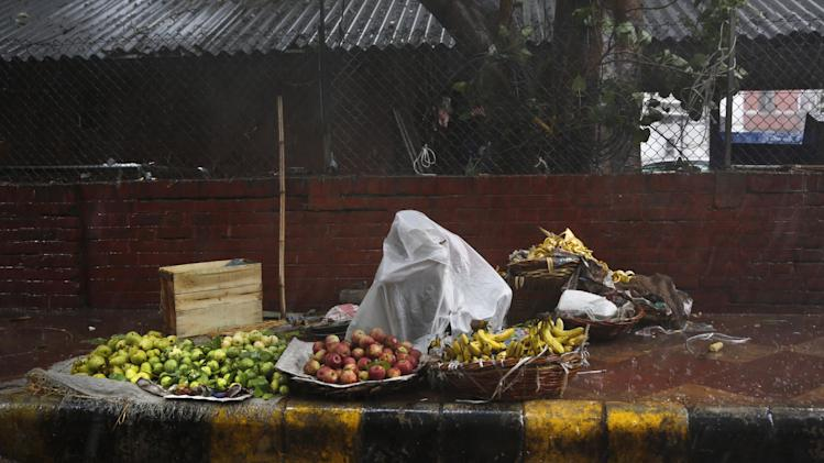 A roadside fruit seller uses a plastic sheet to shelter himself from a sudden downpour in New Delhi, India ,Thursday, Aug. 28, 2014. (AP Photo/Manish Swarup)