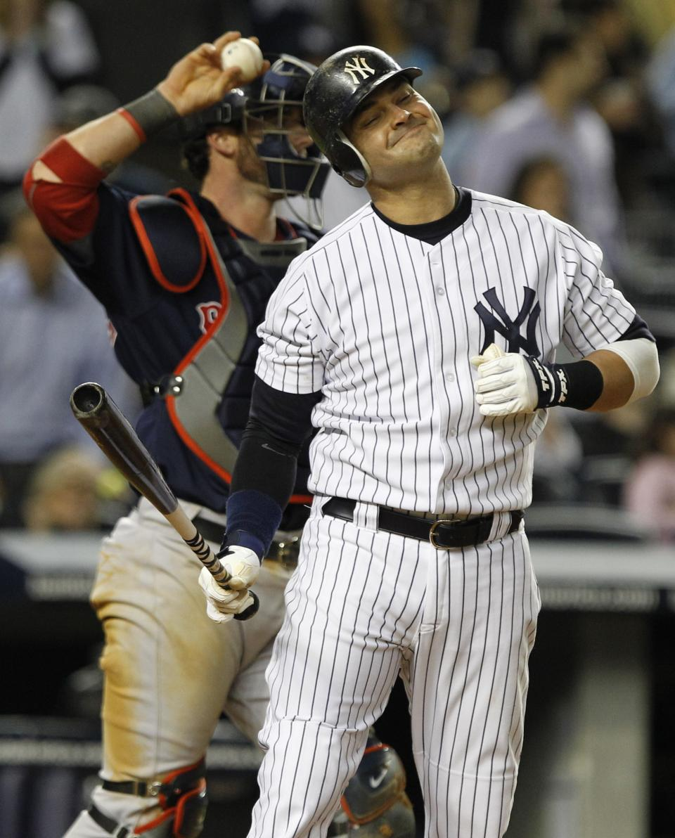 New York Yankees' Nick Swisher reacts after striking out during the eighth inning of a baseball game Boston Red Sox catcher Jarrod Saltalamacchia throws the ball back to the pitcher Friday, May 13, 2011, at Yankee Stadium in New York. (AP Photo/Frank Franklin II)
