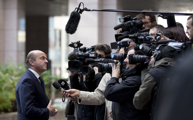Spain's Economy Minister Luis de Guindos, left, speaks with the media as he arrives for a meeting of eurogroup finance ministers at the EU Council building in Brussels on Monday, Nov. 26, 2012. Eurozone finance ministers are set to meet in Brussels on Monday to discuss the next installment of bailout money for debt-laden Greece. (AP Photo/Virginia Mayo
