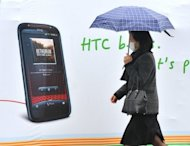 A woman walks past a billboard displaying a handset of Taiwan smartphone maker HTC in Taipei in 2011. Taiwan's leading smartphone maker HTC said it was suing technology giant Apple in the United States, claiming it has infringed on its patents
