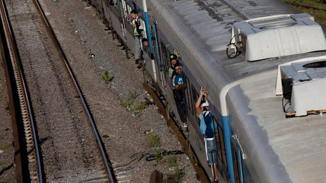 In this Jan. 28, 2013 photo, passengers peer from their wagons as they arrive to Once train station in Buenos Aires, Argentina. Nearly a year after a train crash killed 51 people and injured 800 others on Feb. 22, 2012, exposing systemic corruption and other failures in Argentina's transportation systems, the victims' families and other passengers are as angry as ever over a litany of promised improvements and safety measures that have not been made. (AP Photo/Natacha Pisarenko)