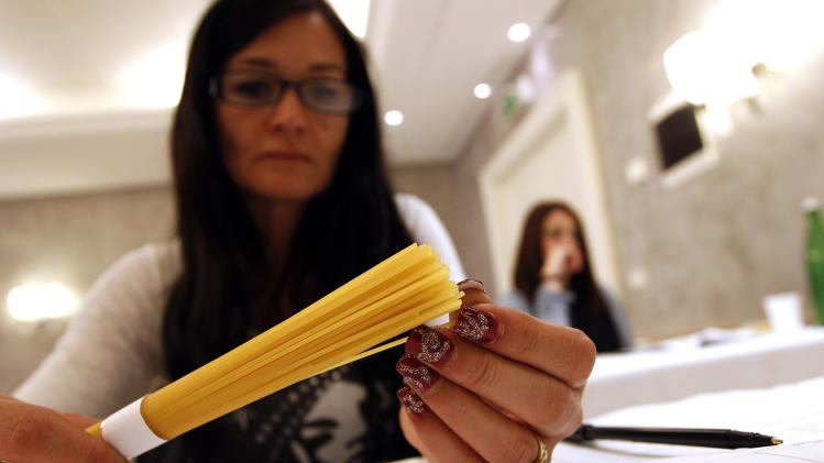 A woman touches pasta in a hotel conference room in Rome, Friday, May 18, 2012. Pasta sales worldwide have grown steadily over the past three years. Pasta is serious business in Italy, and the recent blind taste test organized by the world's biggest pasta maker, Barilla, drove home that an awful lot of thought goes into making the simple combination of durum wheat semolina and water from which Italy's national dish is made. (AP Photo/Alessandra Tarantino)