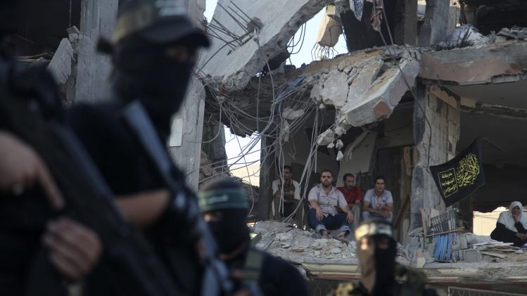 Palestinians watch Hamas militants from inside their house that witnesses said was destroyed during an Israeli offensive, as militants celebrate what they say was a victory over Israel, in the Shejaia neighborhood east of Gaza City