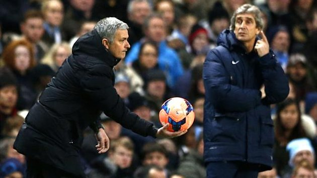 Chelsea manager Jose Mourinho holds the match ball as his Manchester City counterpart Manuel Pellegrini looks on (Reuters)