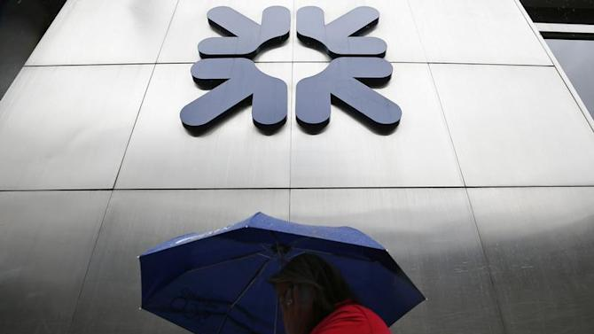 A woman shelters under an umbrella as she walks past a branch of the Royal Bank of Scotland in the City of London