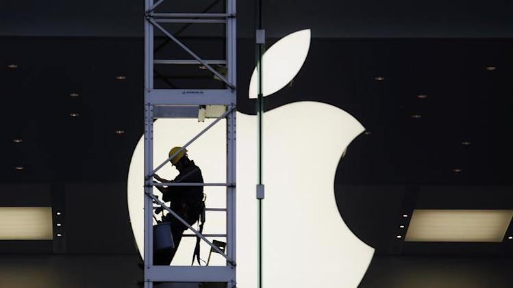 A worker climbs outside an Apple store in Hong Kong