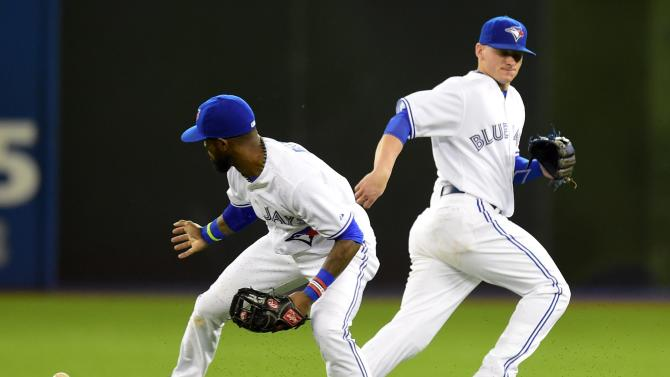 Toronto Blue Jays' Jose Reyes, left, can't handle a Chicago White Sox's Adam LaRoche single as Blue Jays' Ryan Goins runs past during seventh inning American League baseball action in Toronto on Tuesday, May 26, 2015.   (Frank Gunn/The Canadian Press via AP) MANDATORY CREDIT